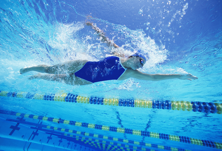 Female swimmer wearing United States swimsuit while swimming in