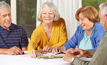 Group of senior people in retirement home playing domino game