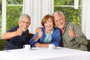 Happy senior people holding thumbs up while drinking coffee in r