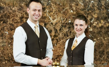 Receptionist or concierge workers standing at hotel counter