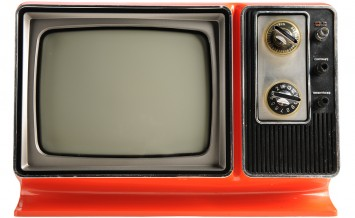 Orange vintage television from the 1970s isolated over white bac