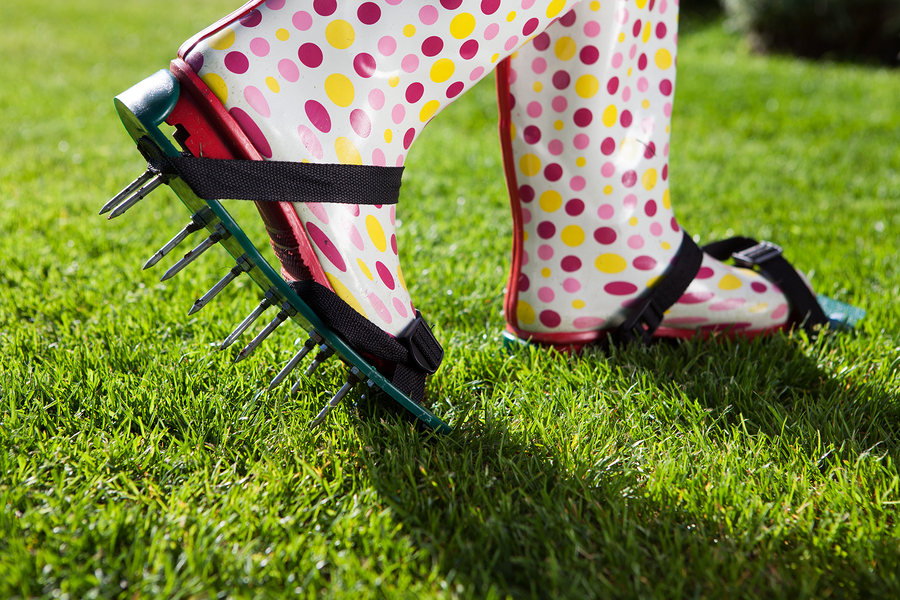 Woman wearing spiked lawn revitalizing aerating shoes, gardening