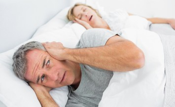Fed up man blocking his ears from noise of wife snoring at home