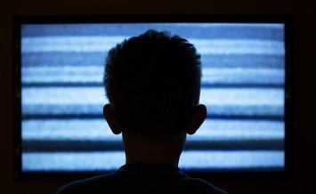 Boy watching television with noise