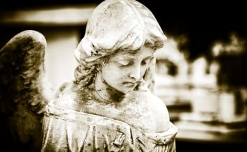 Vintage image of a sad angel on a cemetery with a diffused backg