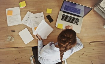 Businesswoman Working At Her Office Desk With Documents And Lapt