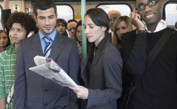Group of multiethnic commuters in a train with woman reading new