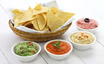 tortilla chips with four super bowl dips which are salsa roja, g