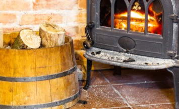Fireplace With Fire Flame And Firewood In Barrel Interior. Heati