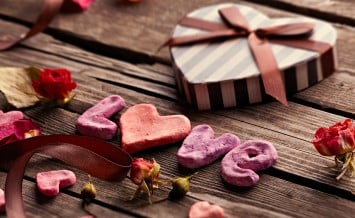 Word Love with heart shaped Valentines Day gift box on old vinta