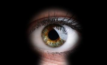 Female eye peeking through a keyhole concept for curiosity, stal