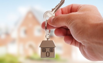 Holding house keys on house shaped keychain in front of a new ho