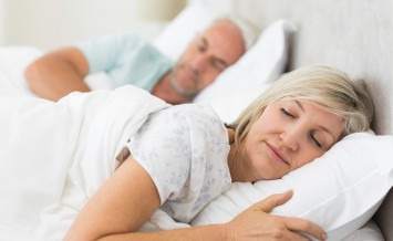 Closeup of a mature couple sleeping with eyes closed in the bed