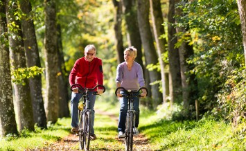 Senior Man and woman exercising with bicycles outdoors, they are