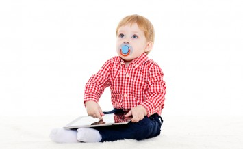 Little sweet child plays with computer tablet on a white background. Learning toys and early development.