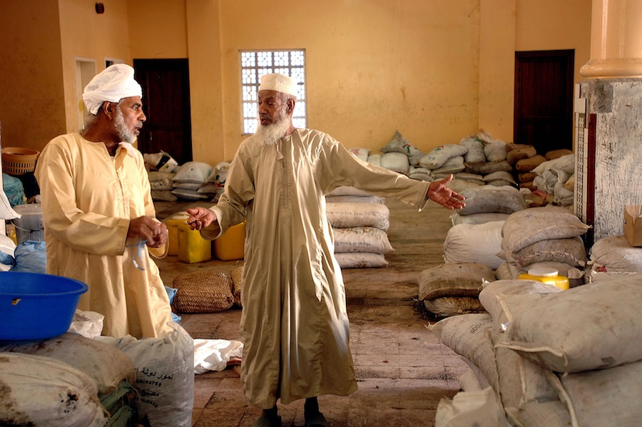 The date market in the souk of Mascat, in the Sultanate of Oman. Two men talking near bags of dates piled up. *** Local Caption ***