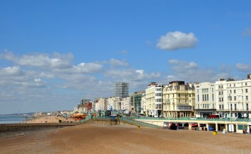 Brighton United Kingdom - April 16 2012: Tourists on the beach enjoying a Spring day at Brighton on the south coast of England.