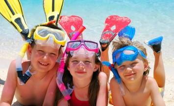 Three smiling children posing on a beach wearing snorkeling equipment.