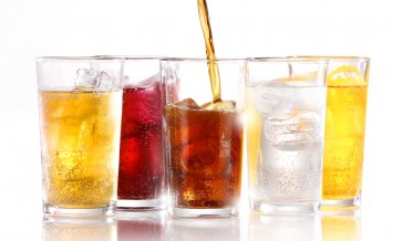 Soft drinks with ice being poured against a bright white background