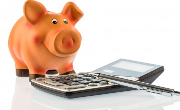 a red pen is on a calculator beside a piggy bank. save on costs, expenses, and budget. interest for savers