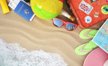Travel concept. Sunbed sunglass  map beach shoes sunscreen passport air tickets beach ball hat and old red suitcase for travel on the beach.