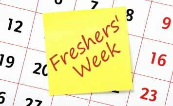 A reminder of Freshers' Week on a yellow sticky note posted to a wall calendar
