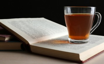 Glass cup of tea with book on wooden table on black background