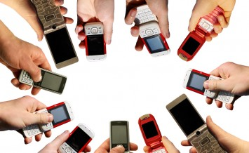 Many hands holding a mobile phones on white