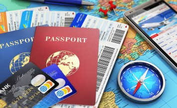 Air tickets or boarding pass, passports, touchscreen smartphone with online airline tickets booking or reservation internet application, magnetic compass, credit cards and pen on world geographic map atlas