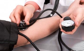doctor checking blood pressure with stethoscope and sphygmomanom