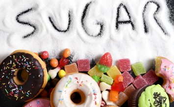 mix of sweet cakes donuts and candy with sugar spread and written text in unhealthy nutrition chocolate abuse and addiction concept body and dental care