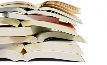 Untidy stack or pile of open paperback books isolated on a white background. Space for copy.