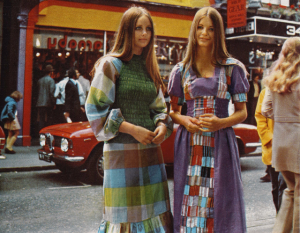 """Fashion was still heavily influenced by the hippie movement of the 1960s and took style cues from ethnic fashions around the world. Tie dye shirts folk embroidered blouses, ponchos, capes and military surplus clothing were all popular items. Bell-bottom trousers and ankle-length dresses known as """"maxis"""" also began to feature prominently. Sweaters also became a huge phenomenon in the early 1970s, and colours like baby blue, peach, camel, forest green, rust and pistachio were among the most popular colours to wear during this time."""