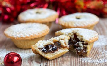 Closeup of an open mince pie on a wooden table with red christmas background