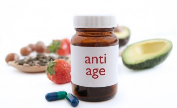 Medecine jar with anti aging pills surrounded by nutritious superfoods including avocado pumpkin seeds and berries