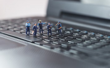 Miniature Police Squad Protecting Laptop Computer. Technology Co