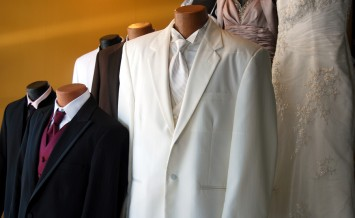 A display of tuxedos and wedding gowns.