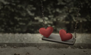Fabric red heart on damage metal playground swing Broken heart concept