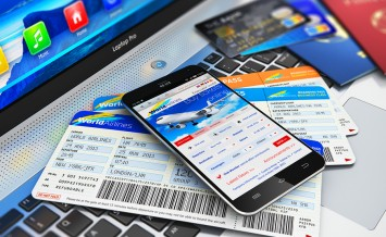Modern touchscreen smartphone or mobile phone with airline internet web site offering booking or buying airliner tickets online, credit cards and passports on laptop or notebook computer PC keyboard