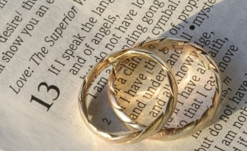 wedding rings belonging to the married couple are displayed on the page of the bible at 1 corinthians 13 - the love chapter