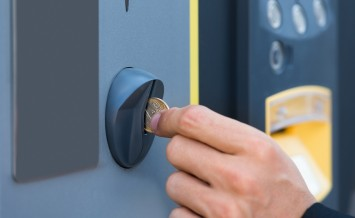Close-up Of Person's Hand Inserting Coin At Parking Meter