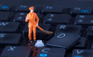 Miniature Worker With Broom Working On Keyboard