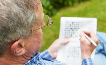 Senior Man Doing Crossword Puzzle In Garden