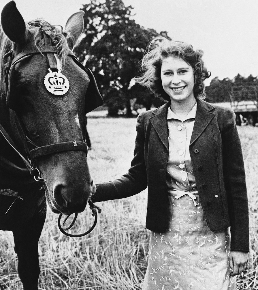 The Queen is known for her passion for horses. She learned to ride as a young princess after she received her first pony, Peggy, from her Grandfather King George V. Here, she is pictured with one of the farm horses at Sandringham several months before her 18th birthday.