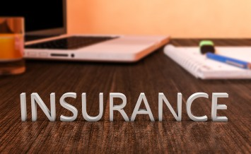 Insurance - letters on wooden desk with laptop computer and a notebook. 3d render illustration. ** Note: Shallow depth of field