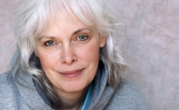 Casual portrait of happy mature woman with natural white hair and minimal makeup.