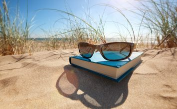 Book and sunglasses on the beach for summer reading and relaxing