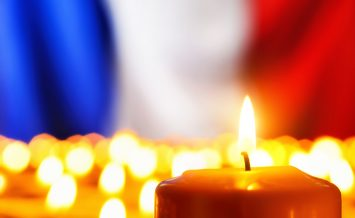 Lots of candles in front of the national colors of France in remembrance of the many victims of terror or to simply symbolize the great French spirit ** Note: Shallow depth of field