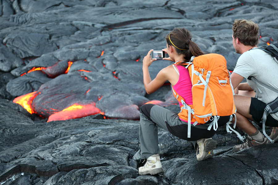 Hawaii lava tourist. Tourists taking photo of flowing lava from