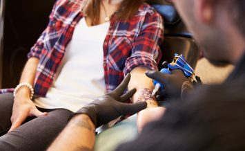 Close Up Of Woman Sitting In Chair Having Tattoo